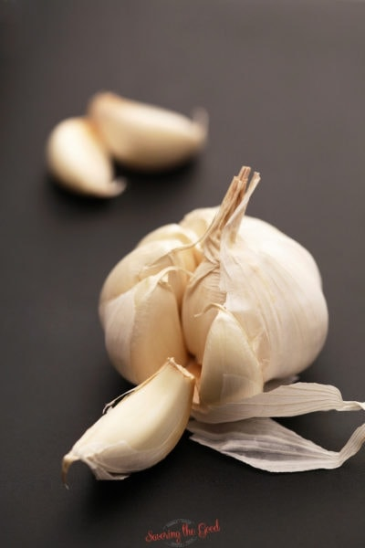 a whole clove of garlic on a grey surface