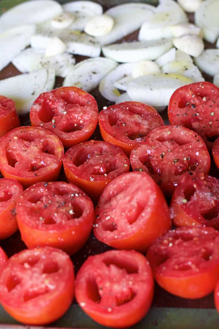 fresh tomatoes onions peeled garlic on a sheet tray