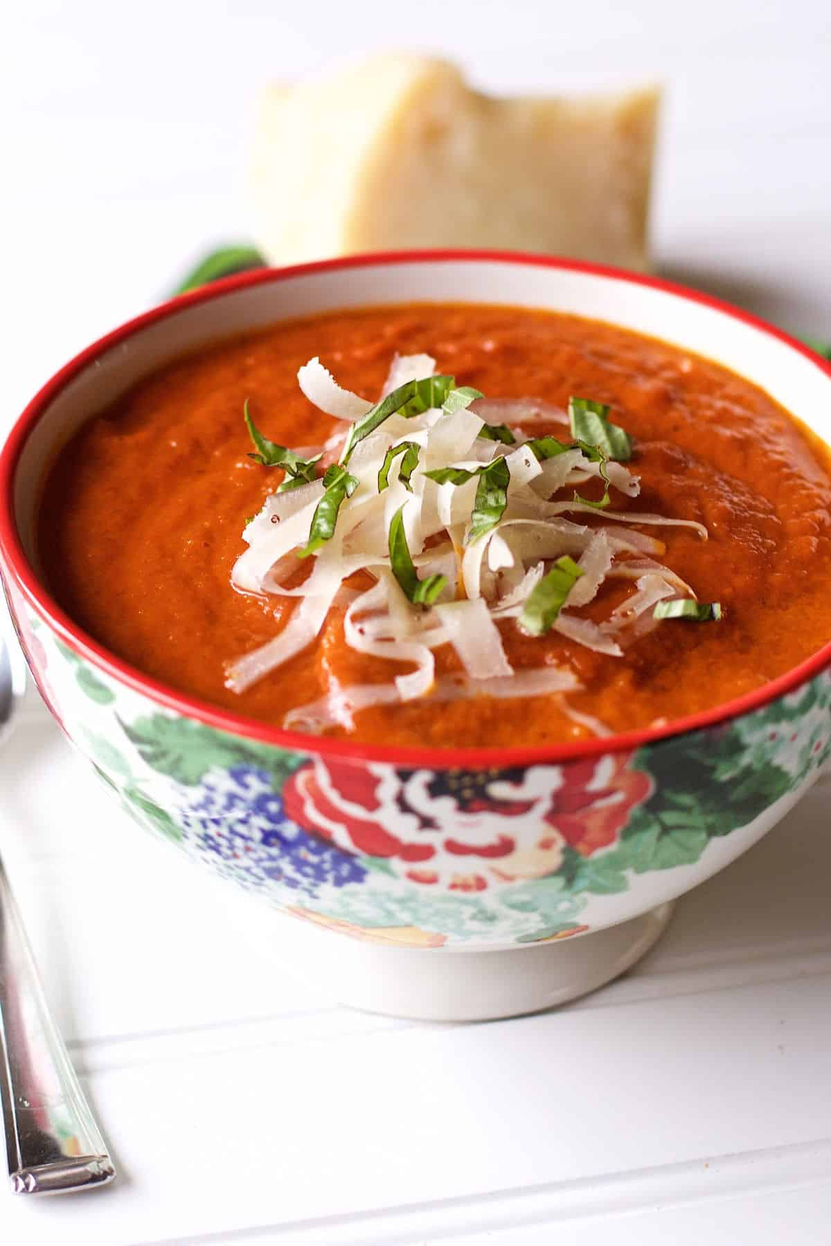 The best oven roasted tomato soup with parmesan chunk to the upper right of the bowl