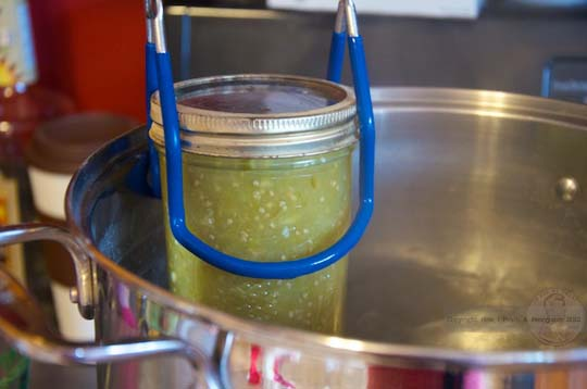 salsa verde in mason jar being lowered into the boiling water with blue tongs