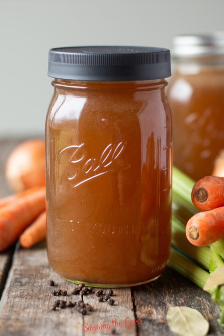 vertical image of vegetable stock in a ball canning jar.