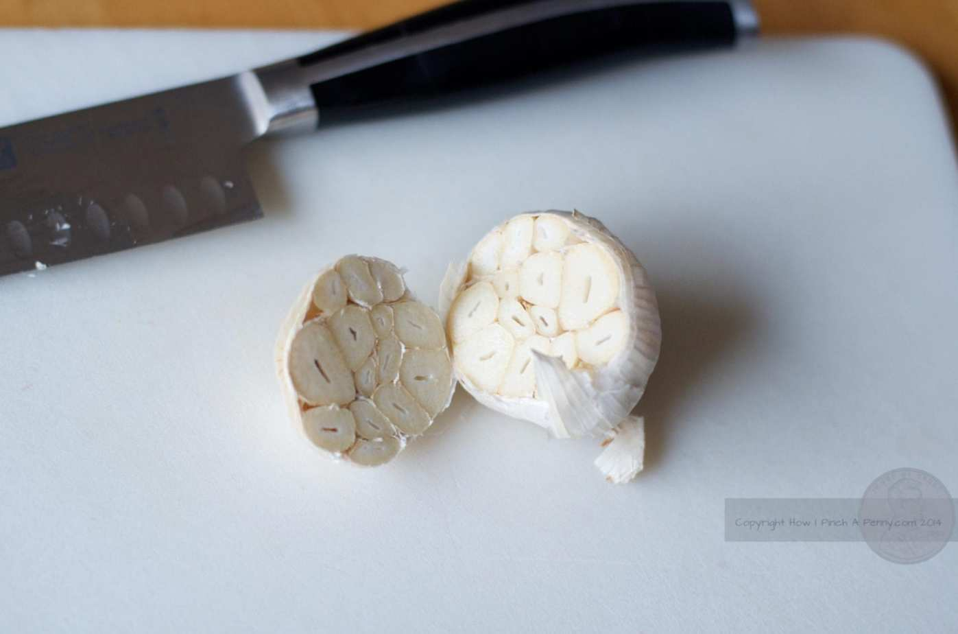 bulb of garlic sliced open on a white cutting board