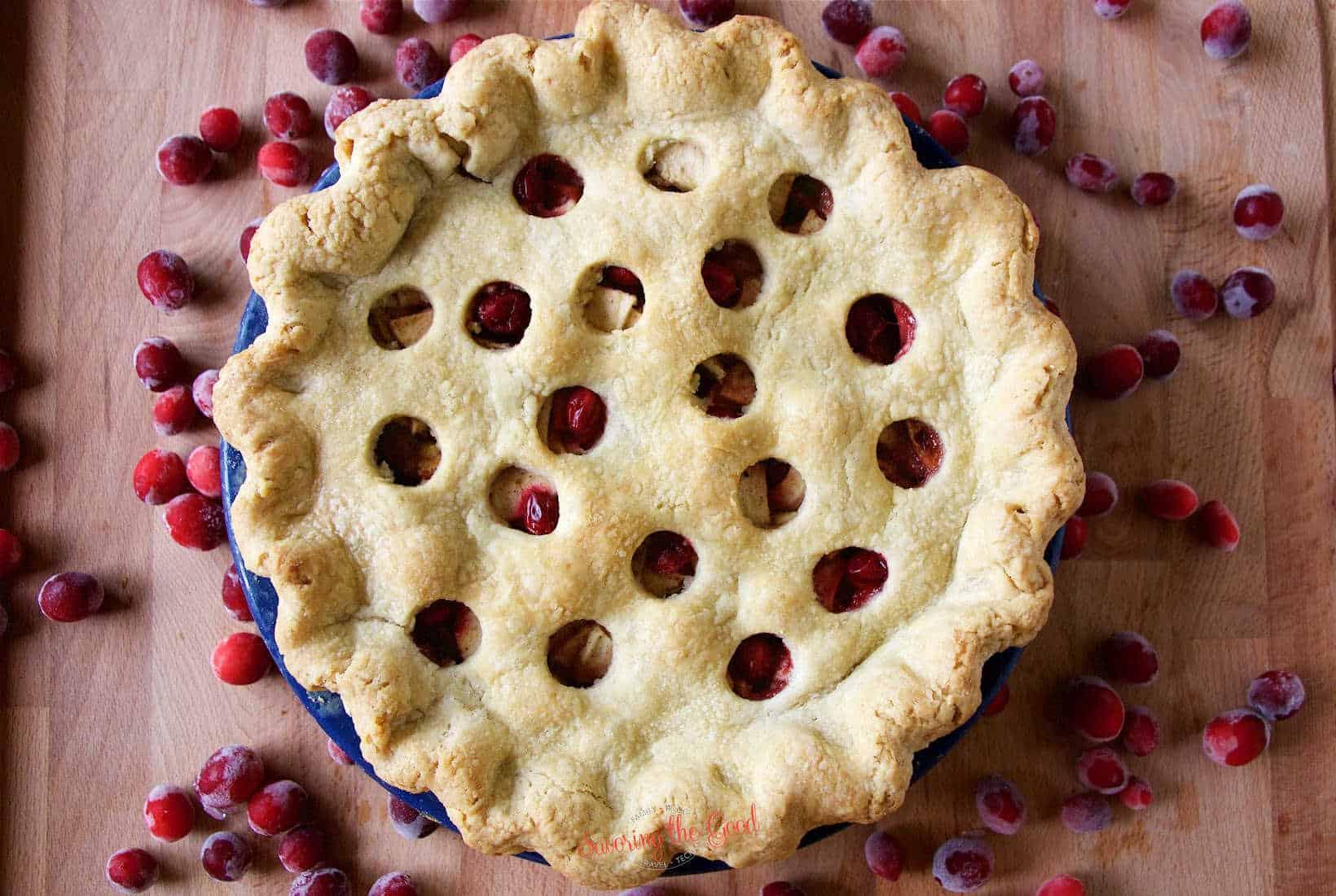 full apple cranberry pie in a blue pie plate