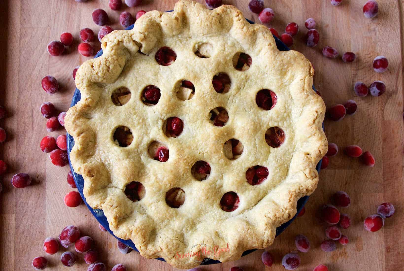 fully baked double crust apple cranberry pie in a blue pie plate on a wooden cutting board with whole cranberries scattered around