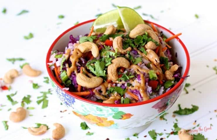 spicy thai peanut rice salad in a bowl with lime and cashew garnishes