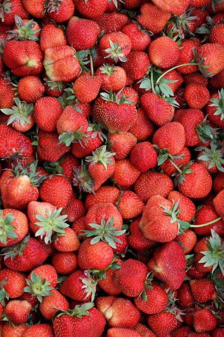 fresh strawberries, green tops, stems on