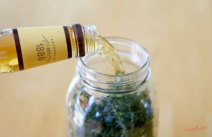 bourbon being poured into a jar filled with thyme