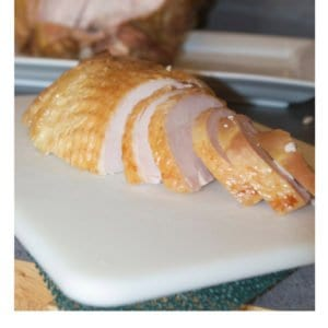 carved turkey breast on a white cutting board