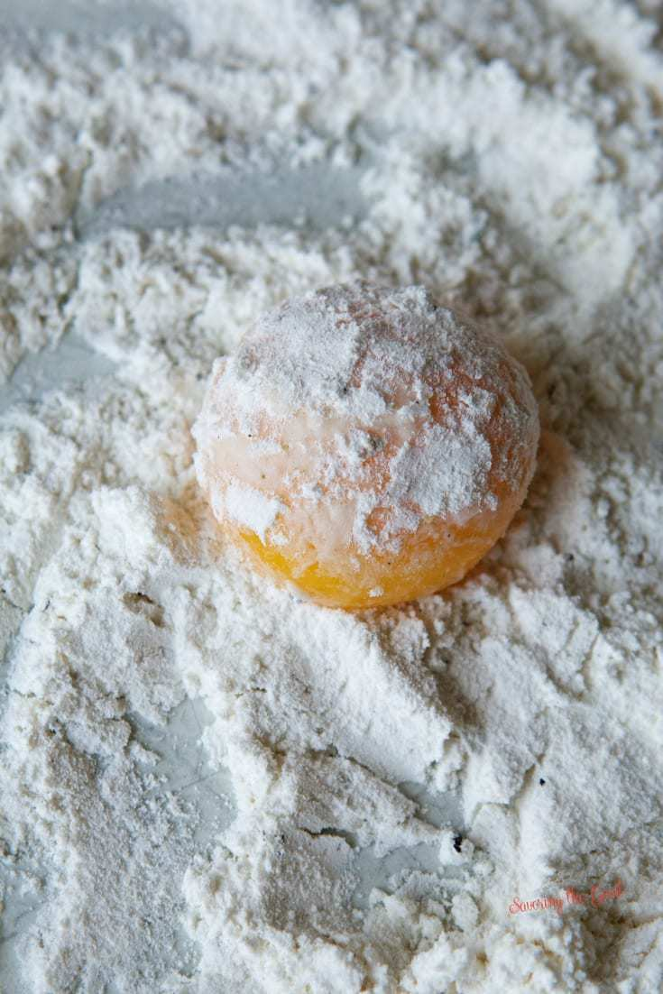 Egg Yolk Croquette getting dredged in flour