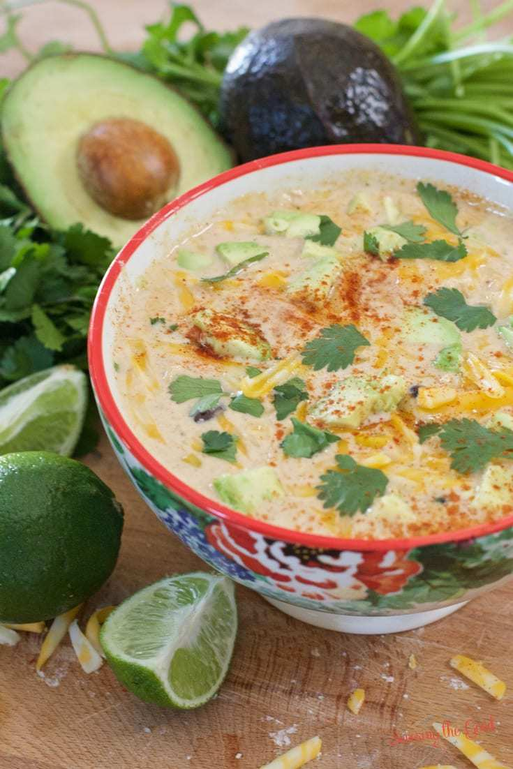 This crockpot Mexican corn soup has layers of flavor that include shredded chicken, black beans, creamed corn, Mexican spices as well as a creamy broth. Top this easy slow cooker soup with your choice of fresh squeezed lime, avocado, cilantro, sour cream andjalapeño. Crockpot Mexican corn and chicken soup is sure to bring your favorite fiesta flavors to your table. #crockpot #slowcooker #crockpotsoup #mexicanstreetcornchowder #slowcookersoup #soup