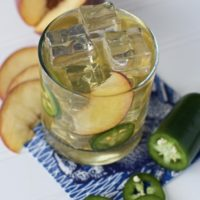 This spicy peach bourbon smash cocktail is a delicious summer bourbon cocktail made with fresh peaches and smashed jalapeños. Sweetened with jalapeño infused honey, this peach whiskey drink goes down smooth and ends with a kick of heat. Summer isn't complete with out a peach whiskey drink. #peachcocktail #bourbonsmash ##summercocktail #bourboncocktail #peachsmash
