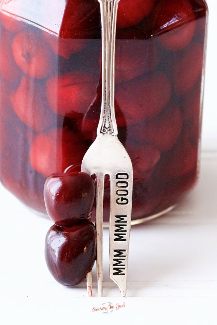 bourbon soaked cherries on a silver folk leaning on a jar of homemade bourbon soaked cherries