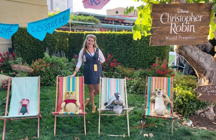 Christopher Robin Red Carpet sarah mock with Christopher Robin characters in chairs