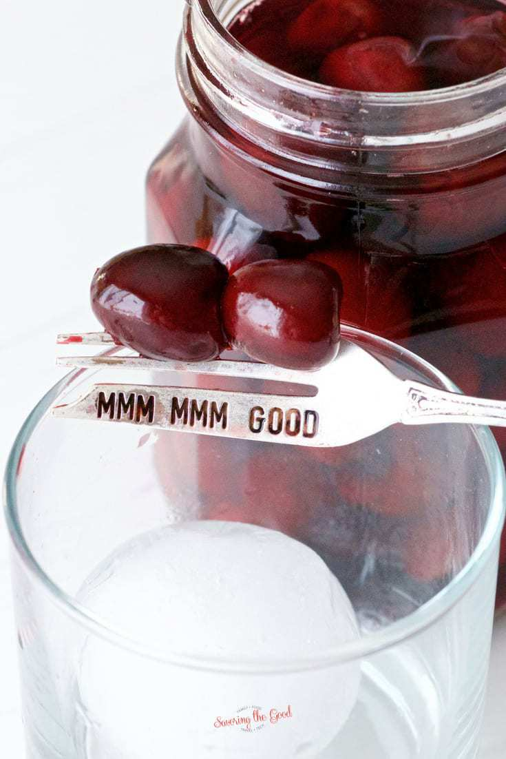 bourbon soaked cherries on a fork garnishing a glass