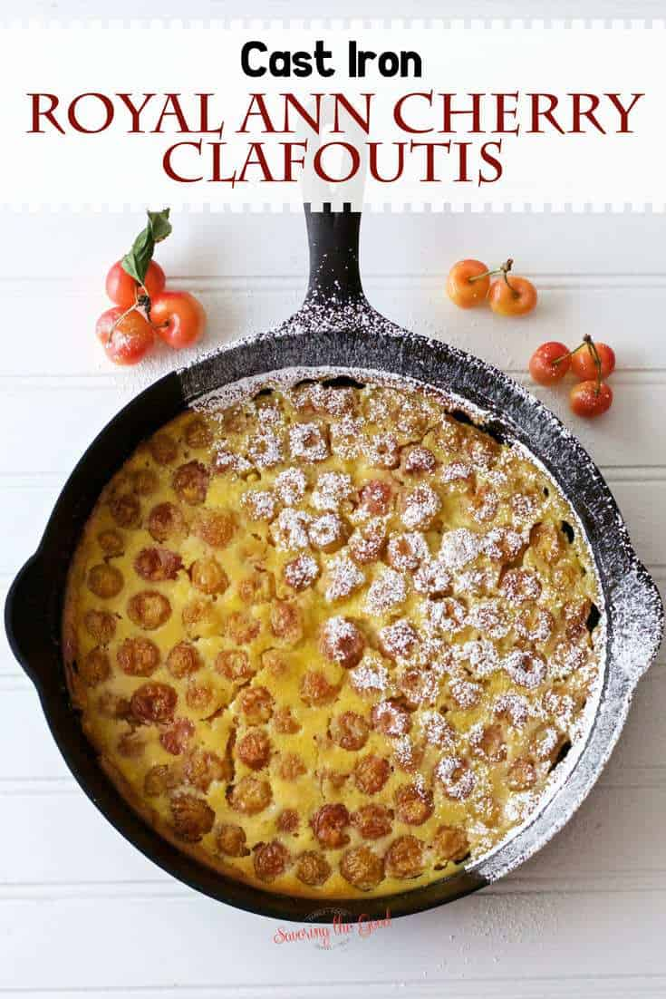 Royal Ann Cherry Clafoutis in cast iron pan with powdered sugar on white surface with text overlay