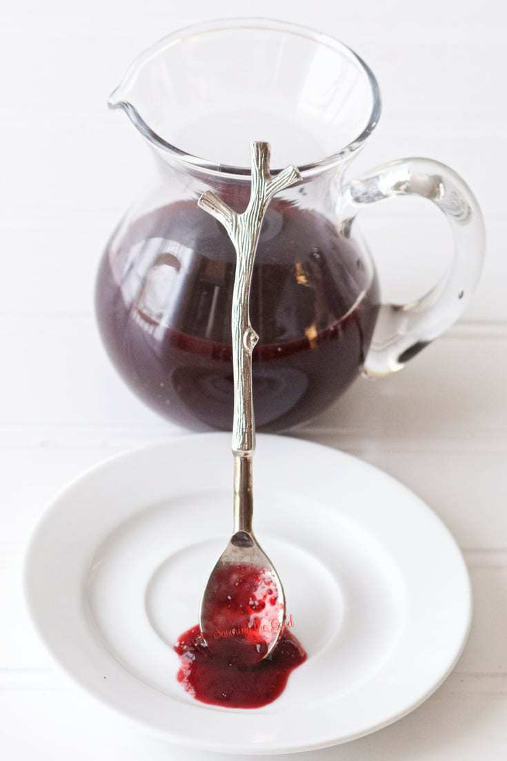cherry syrup in a glass pitcher with a silver spoon resting along side it showing texture of the cherry syrup