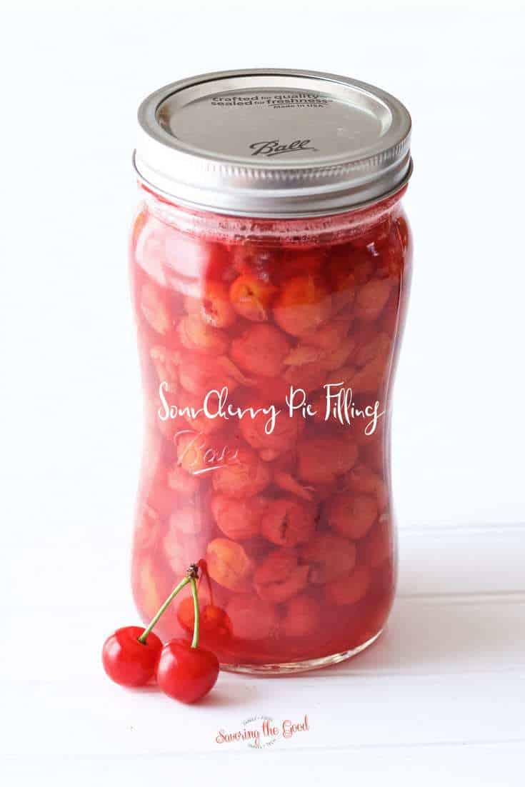 Sour Cherry Pie Filling in a glass ball quart jar. two fresh sour cherries for garnish. with text across the jar.