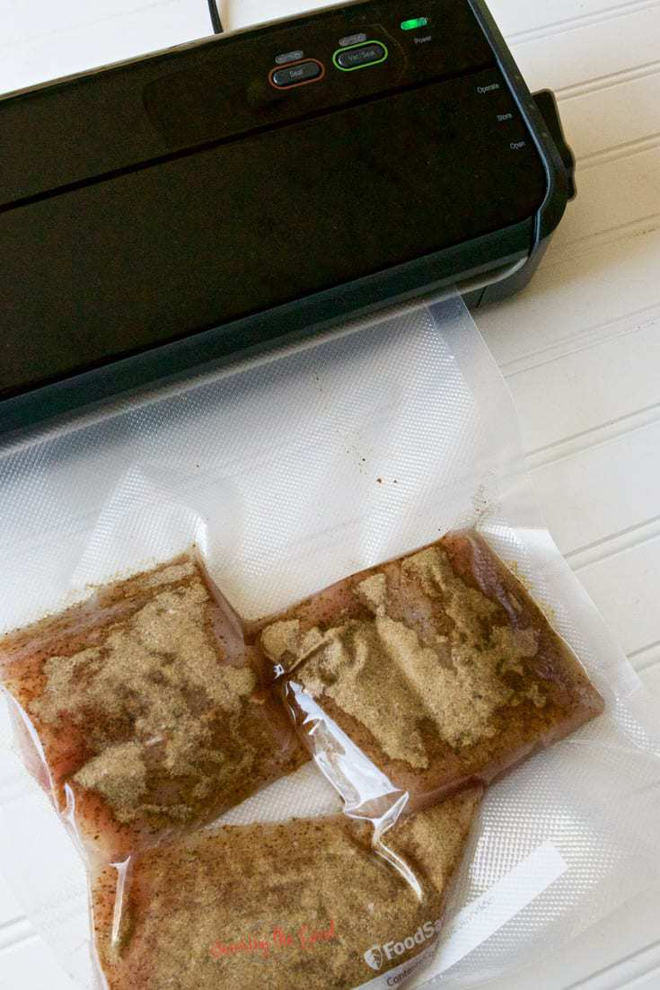 sous vide system with mahi mahi fish in a food saver bag.