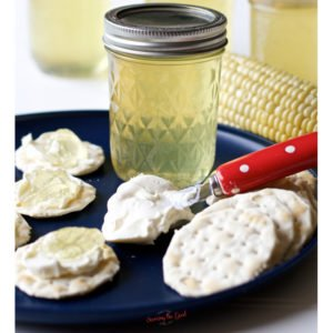 Corn Cob Jelly with water crackers on a blue plate