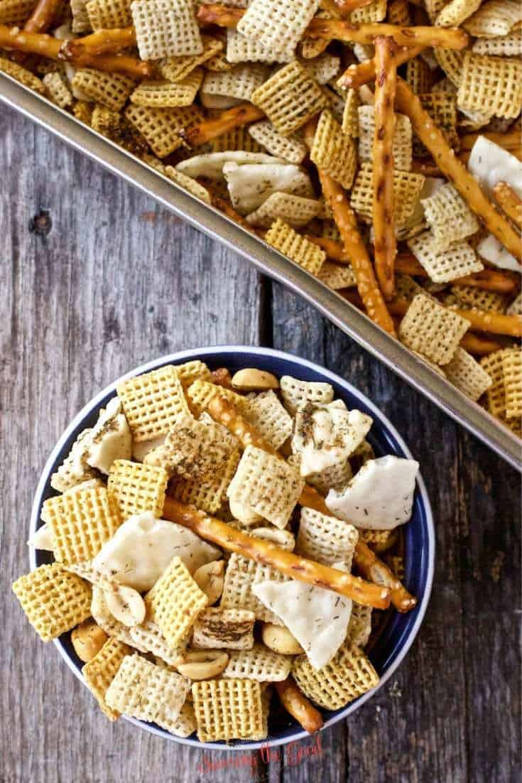 Dill Pickle Chex Mix in a blue bowl with Dill Pickle Chex Mix in a pan to the side