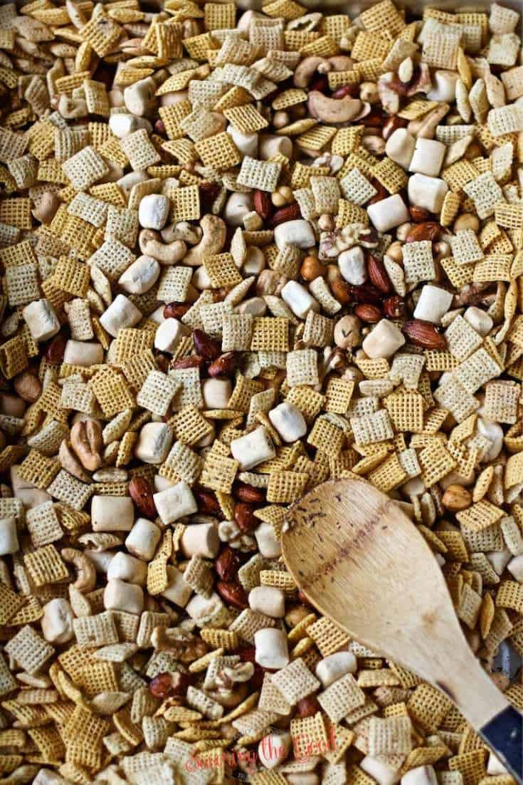 Rosemary and Thyme Chex Mix being mixed with a bamboo spoon