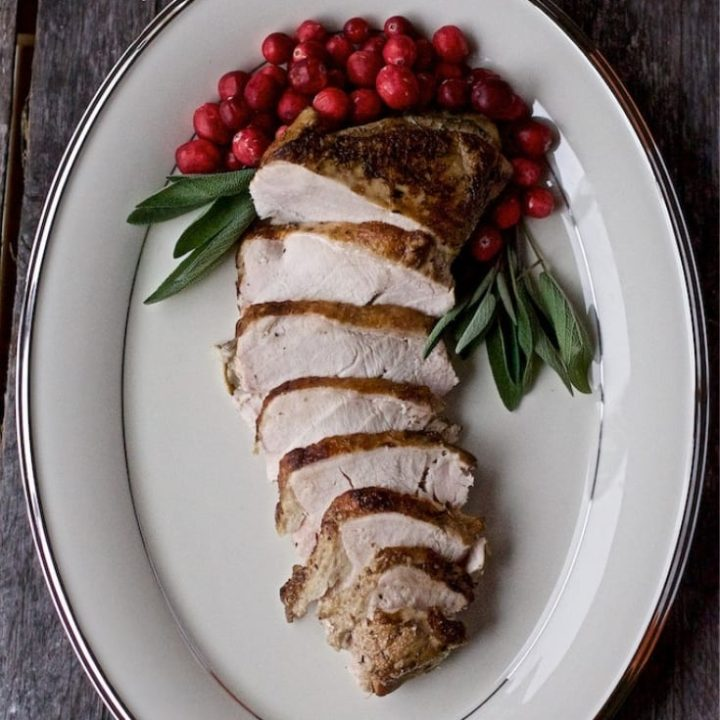 TheBest Sous Vide Turkey Breast on a Lenox serving platter on a wooden surface.