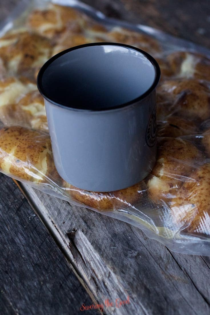Sous Vide Potatoes being smashed with a grey coffee cup in the bag