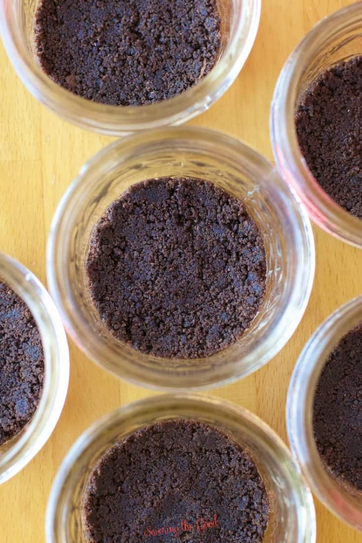chocolate graham cracker crumb crust in the bottom of glass jars