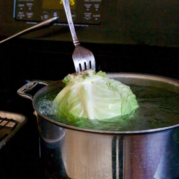 head of cabbage in a pot of boiling water.