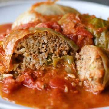stuffed cabbage rolls on a plate with one sliced open showing the inside of one roll