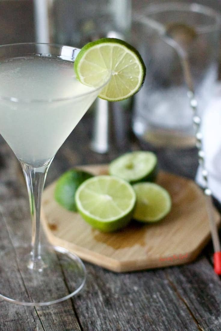 Gimlet cocktail in martini glass with lime wheel garnish