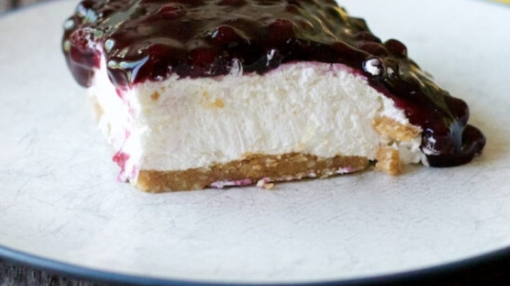 slice of Blueberry Delight on a white plate with a yellow napkin in the background