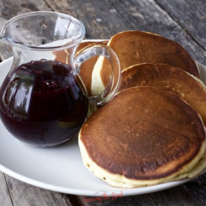 Blueberry Syrup in a jar next to a stack of pancakes, horizontal image