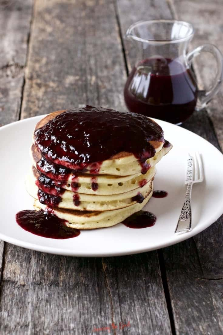 Blueberry Syrup on a stack of 4 pancakes on a white plate