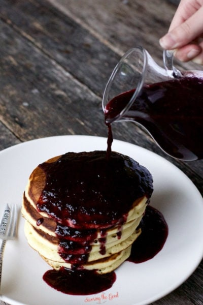 Blueberry Syrup being poured over pancakes from a clear glass pitcher