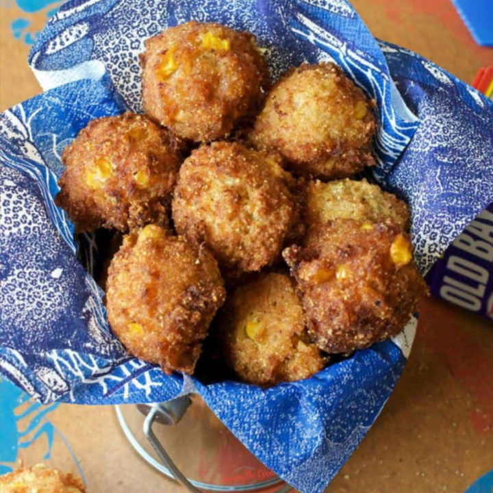Crab Fritters Recipe (corn fritters with crab) in a basket lined with a blue paper napkin