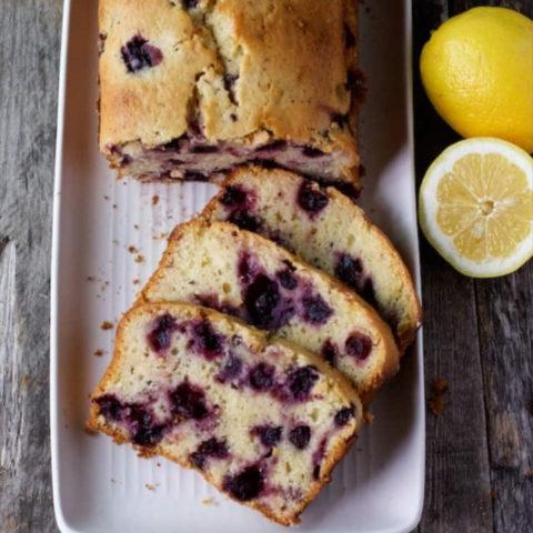 Lemon Blueberry Bread sliced on a white plate with sliced lemons for garnish