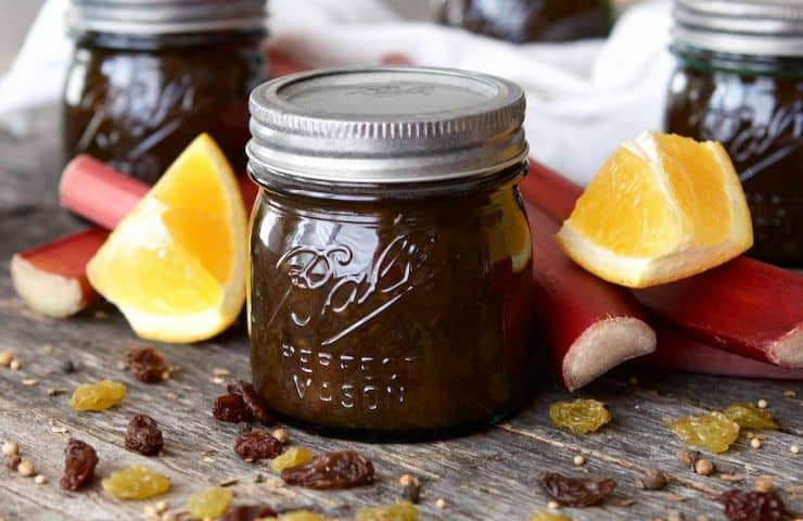 horizontal image of Rhubarb Orange Chutney Recipe in a ball canning jar with raisins in the foreground