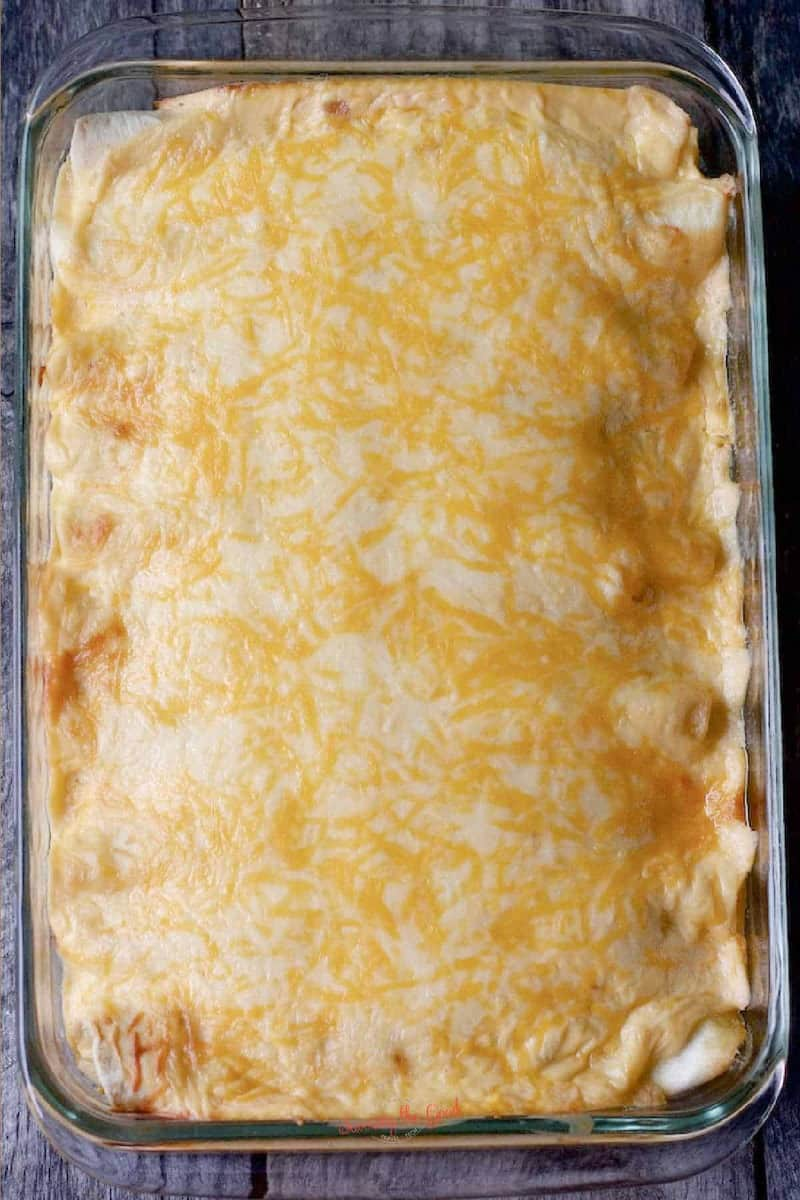 sour cream chicken enchiladas in a casserole dish with melted cheese before garnish