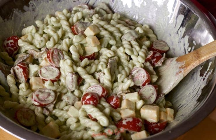 Dill Pickle Pasta Salad being mixed in a stainless bowl with bamboo spoon