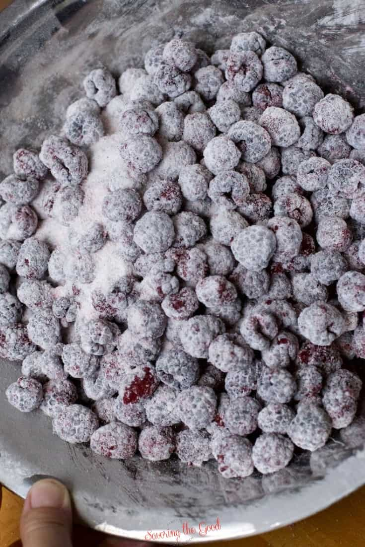 black raspberries coated in corn starch and sugar in a silver colored mixing bowl.