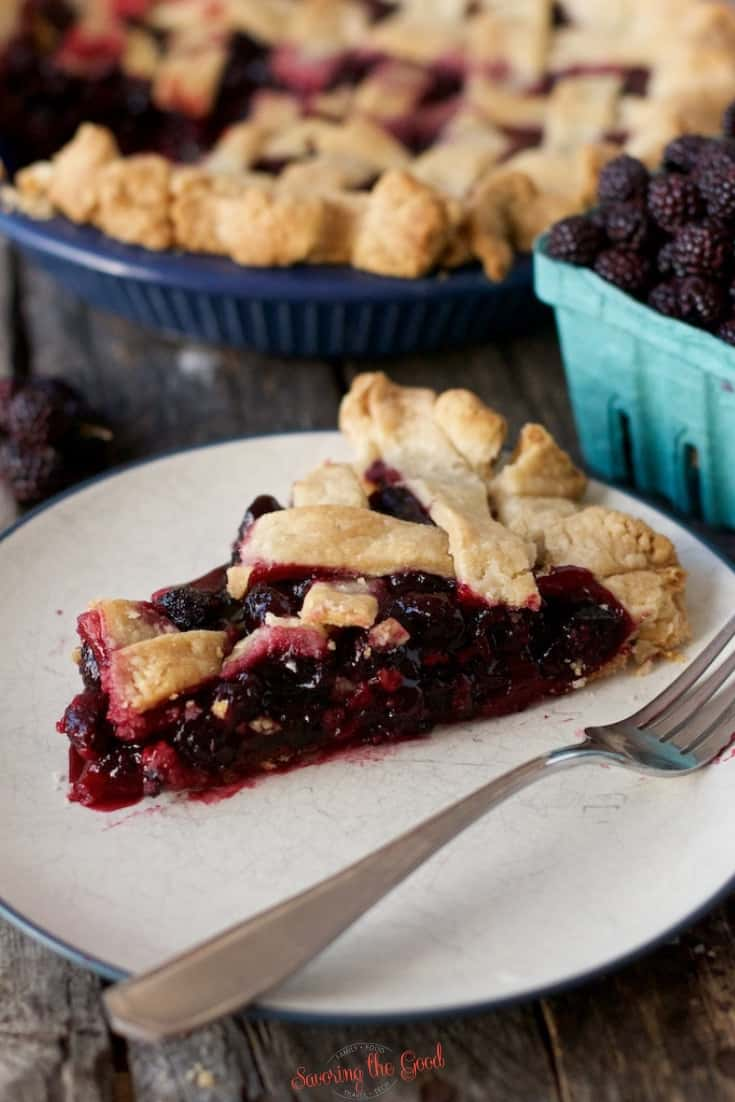 black raspberry pie slice, vertical image, pie and berries in a container in the background