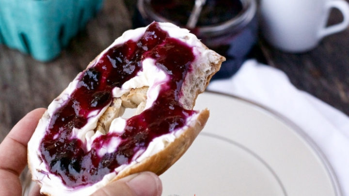bagel with cream cheese and blueberry jam , bite taken out of it.