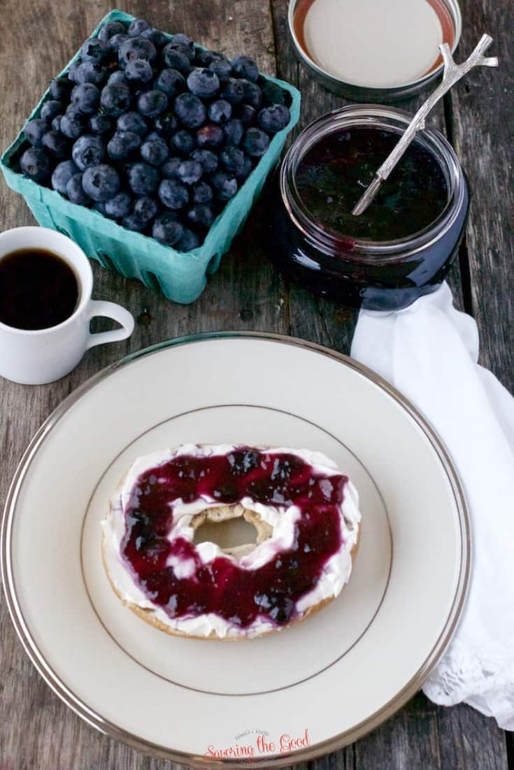 blueberry jam on a bagel with cream cheese on a site plate with fresh blueberries and jar of jam in the background