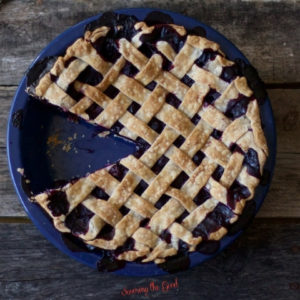 horizontal image of image of blueberry pie recipe with a piece removed on a dark rustic wood surface.