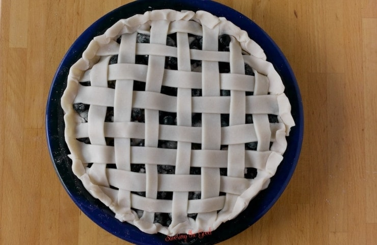 horizontal image of a raw lattice topped blueberry pie