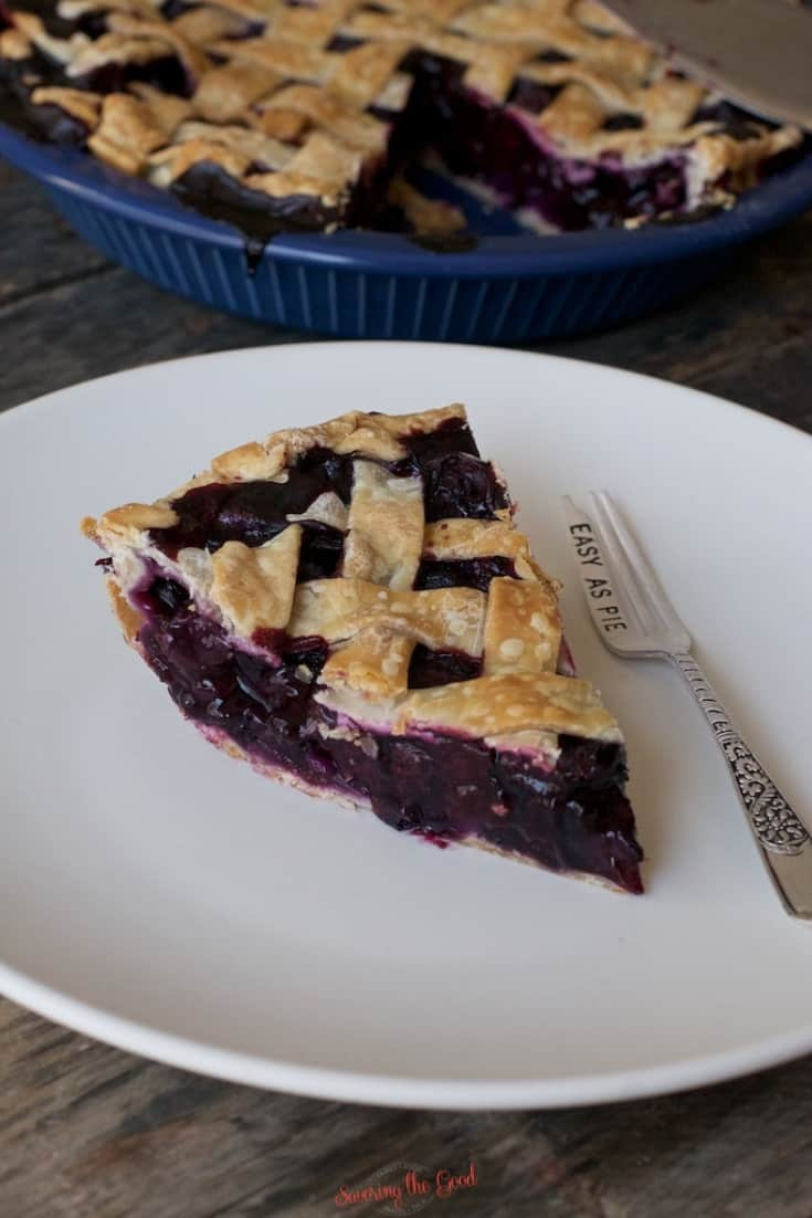 blueberry pie sliced and displayed with a fork on a white plate, rest of the blueberry pie in the background