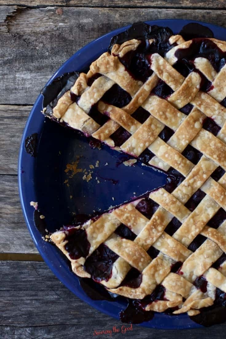 vertical image of blueberry pie recipe with a piece removed on a dark rustic wood surface.