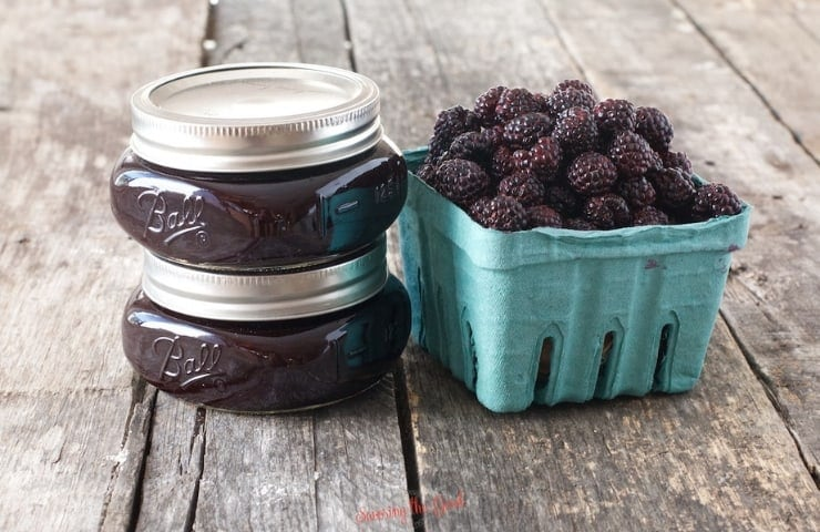 horizontal image of seedless black raspberry jam in 2 jars with a pint of fresh berries to the right side