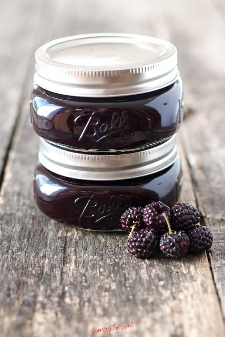 2 half pint jars of seedless black raspberry jam stacked on top of each other